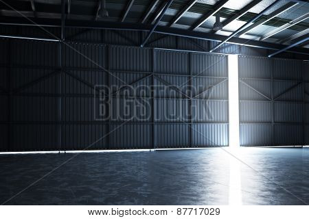 Empty building hanger with the door cracked open