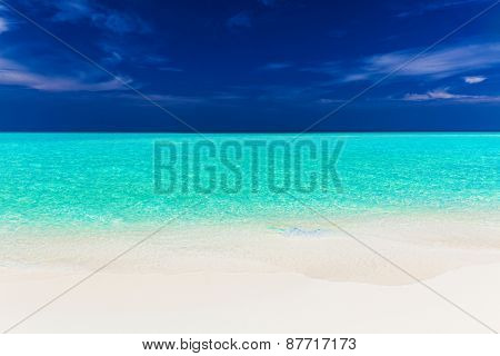 A vibrant shot of clear empty beautiful tropical beach with blue sky