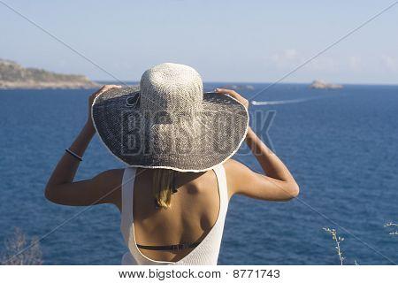 menina com chapéu, olhando para o mar