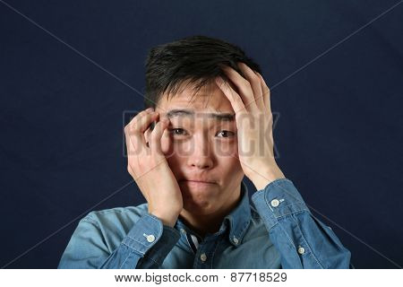 Disappointed young Asian man looking at camera