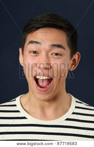Astonished young Asian man laughing and looking at camera