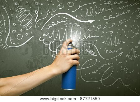 Hand drawing curly lines and arrows on the wall