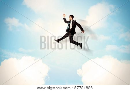 Business person jumping over clouds in the blue sky concept