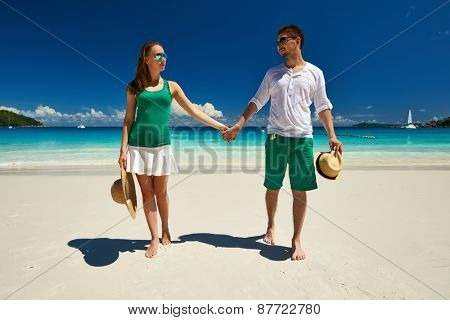 Couple in green walking on a tropical beach at Seychelles