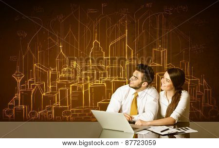 Business couple sitting at the black table with hand drawn buildings and numbers on the background