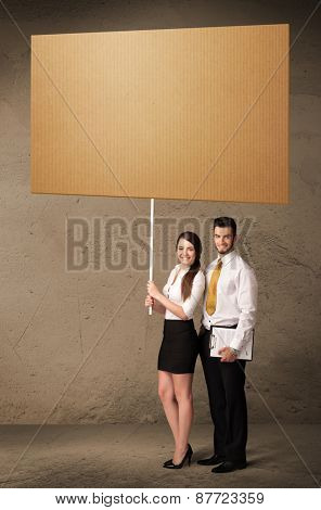 Young business couple holding a blank cardboard