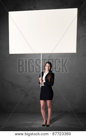 Young businesswoman holding a blank whiteboard