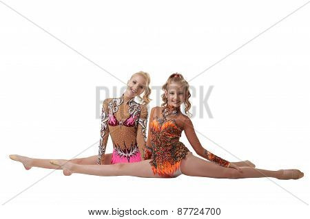 Flexible artistic gymnasts posing at camera