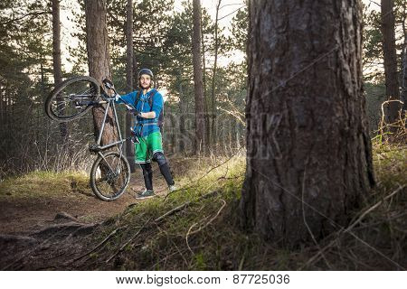 Mountain biker cycling standing by an off road trail through the woods in the late afternoon