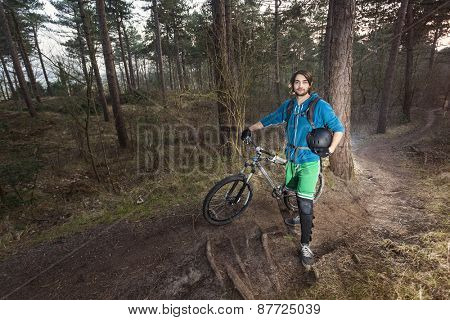 Young man standing in the forest posing proudly with his ATB bike