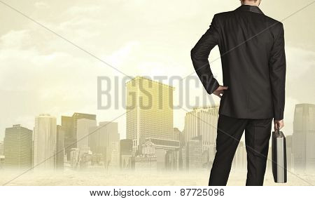 Businessman from the back in front of a city view with sunshine