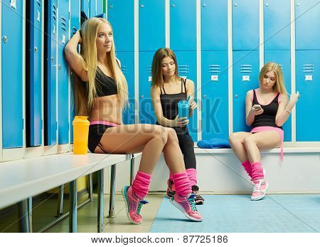 Cute girls resting in locker room after workout