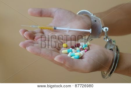 Syringe And Drugs In Hand And Handcuffs