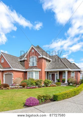 Luxury brick house with a two-car garage and beautiful landscaping on a sunny day.