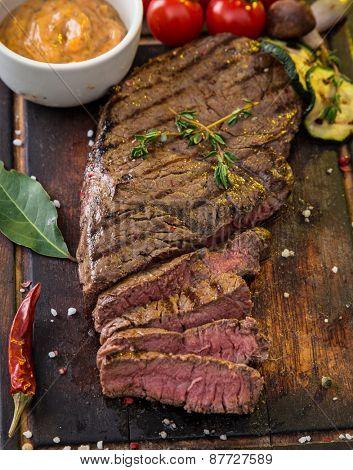 Beef rump steak on black stone table, close-up.
