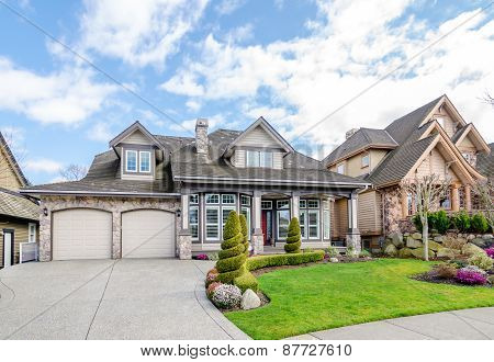 Luxury house with a two-car garage and beautiful landscaping on a sunny day.