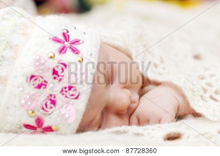 Cute Baby Lying In Hat On Bed Under Soft White Knitted Shawl While Sleeping