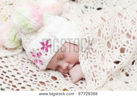 Baby In Hat Lies On Bed Under Soft White Knitted Shawl And Sleeps