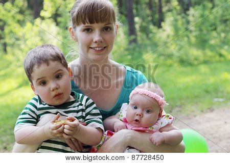 Happy Young Mother With Two Surprised Kids In Summer Sunny Forest