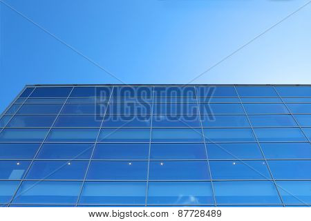 Glass Wall Of Building With Reflection Of Blue Sky With Small Clouds