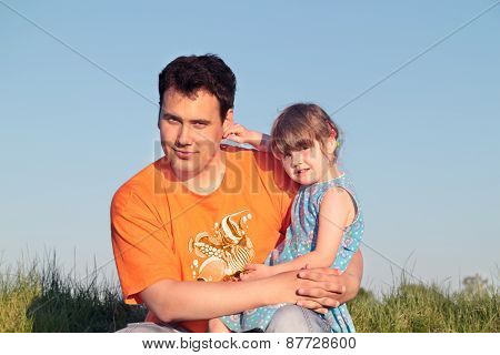 Father And Daughter Sitting In Green Meadow In Sunny Summer Day