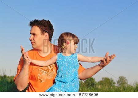 Father And Daughter Sitting In Meadow And Look In Different Directions