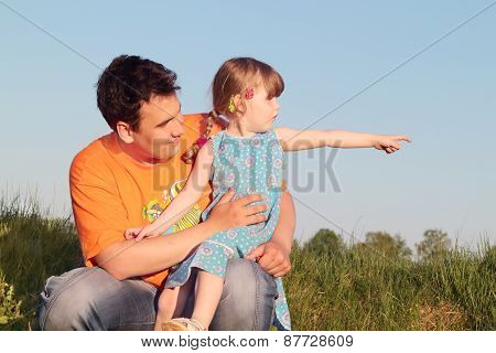 Father And Daughter Sitting In Meadow And Look In One Direction