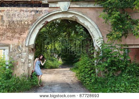 Girl In Beautiful Pose In Dress Stands Near Arch And Green Grass