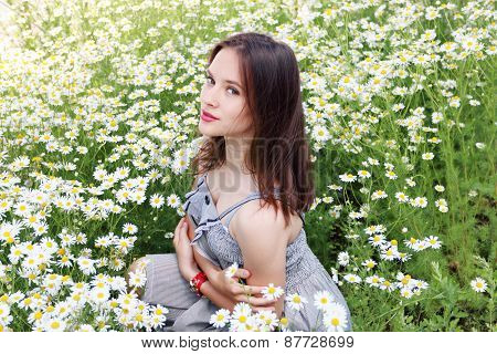 Beautiful Girl With Clock On Hand In Dress Sits In Chamomile Flowers