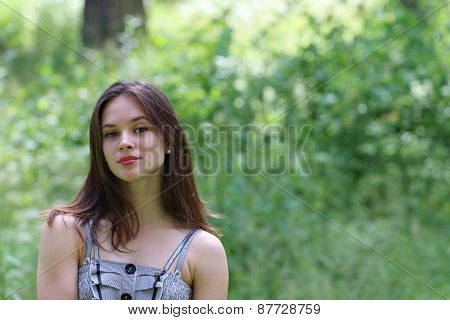 Close-up Of Beautiful Girl In Dress And Long Hair With Blurred View Of Forest In Background
