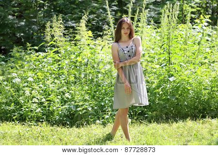 Beautiful Girl In Dress Standing In Woods Amid Tall Grass And Trees