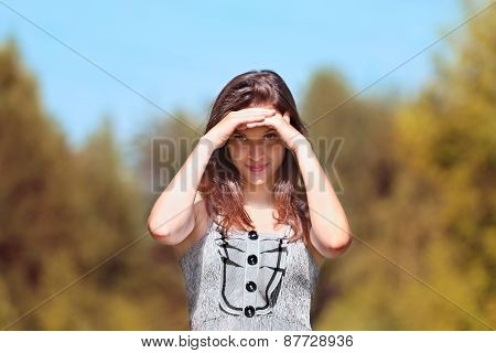 Beautiful Girl In Dress Stands And Looks At Camera With Her Hands Folded Protecting Eyes From Sun