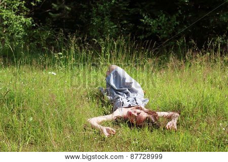 Beautiful Girl In Dress Lying On Meadow In Woods And Looking At Camera