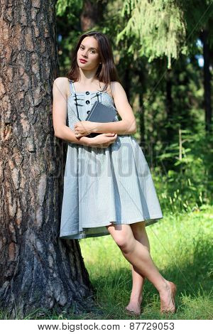 Beautiful Girl In Dress Standing Leaning Against Tree With Book And Looking At Camera
