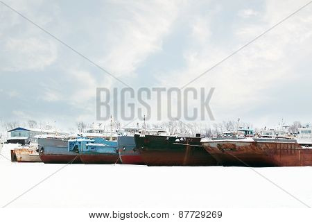 Old And Rusty Big Freight Ships On Frozen River At Winter Cloudy Day