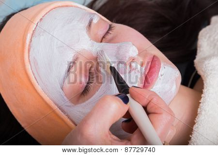 Spa therapy for young woman receiving facial mask at beauty salon.