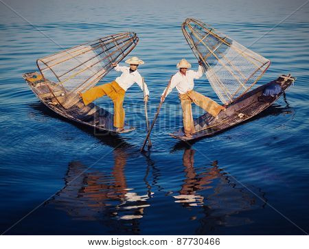 Myanmar Traditional Burmese fishermen balancing with fishing nets at Inle lake,Myanmar famous for their distinctive one legged rowing style. Vintage filtered retro effect hipster style image