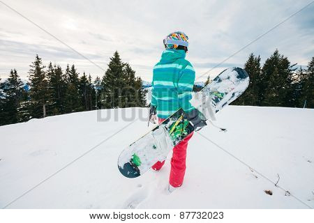 Rear view of female snowboarder with snowboard in hand standing on top of ski slope looking on ski track