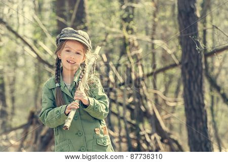 little cute girl near her hut in the forest close-up. Photo in retro style