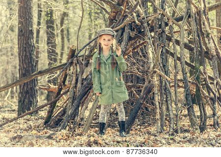 little cute girl near her hut in the forest. Photo in retro style
