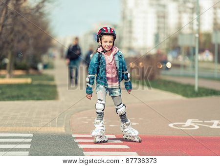 little cute girl riding on roller skates on the bike path