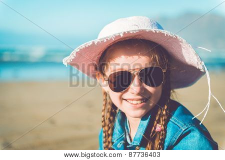 little girl in denim clothing  and hat on a sandy beach