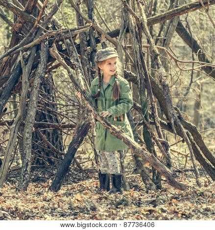 ittle cute girl builds a hut in the woods. Photo in retro style