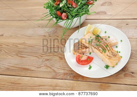 healthy fish cuisine  : grilled pink salmon steaks with vegetable salad on white dish over wooden table