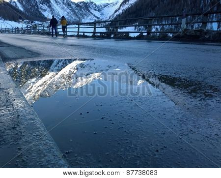 Mountain reflected in the water of a puddle