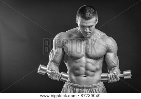 Muscular man working out with weights in gym