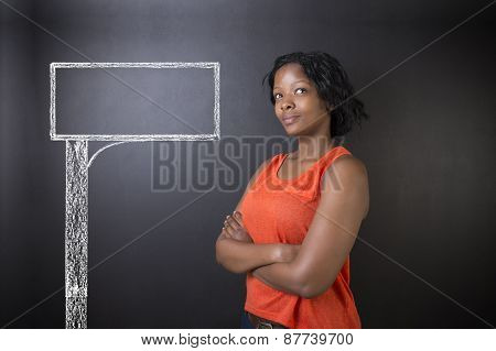 South African Or African American Woman Teacher Or Student With Chalk Road Advertising Sign
