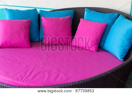 Pink And Blue Pillow On Brown Rattan Sofa