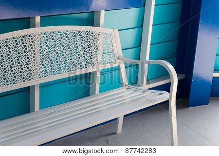 White Metal Seat Beside Blue Wall