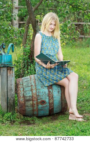 Barefoot Student Girl In Garden Is Reading Book With Blue Cover